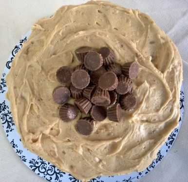 Reese's peanut butter cups mounded in the center of the peanut butter frosting, gracing 3 layers of chocolate cake.