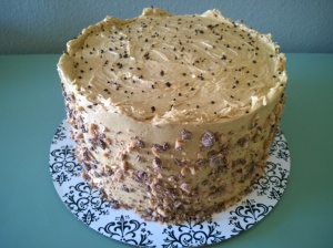 Moist chocolate cake is filled with layers of caramel espresso buttercream and salted caramel, then frosted with the caramel espresso buttercream, and accented with smashed Heath bars and coffee salt.